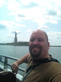 Smiling man on ferry with Statue of Liberty in the distance over his right shoulder
