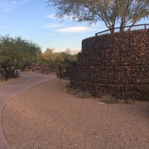 Desert landscaping with curved concrete path leading into the distance. To the right a wall of steel rebar cages filled with river rocks.