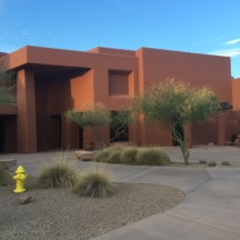 Orange southwest styled conference building with desert landscaping in front.