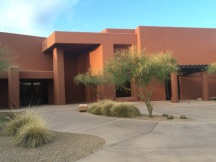 Orange southwestern style conference center with desert landscaping in front.