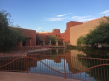 Southwest style hotel with large water feature and desert landscaping in front.